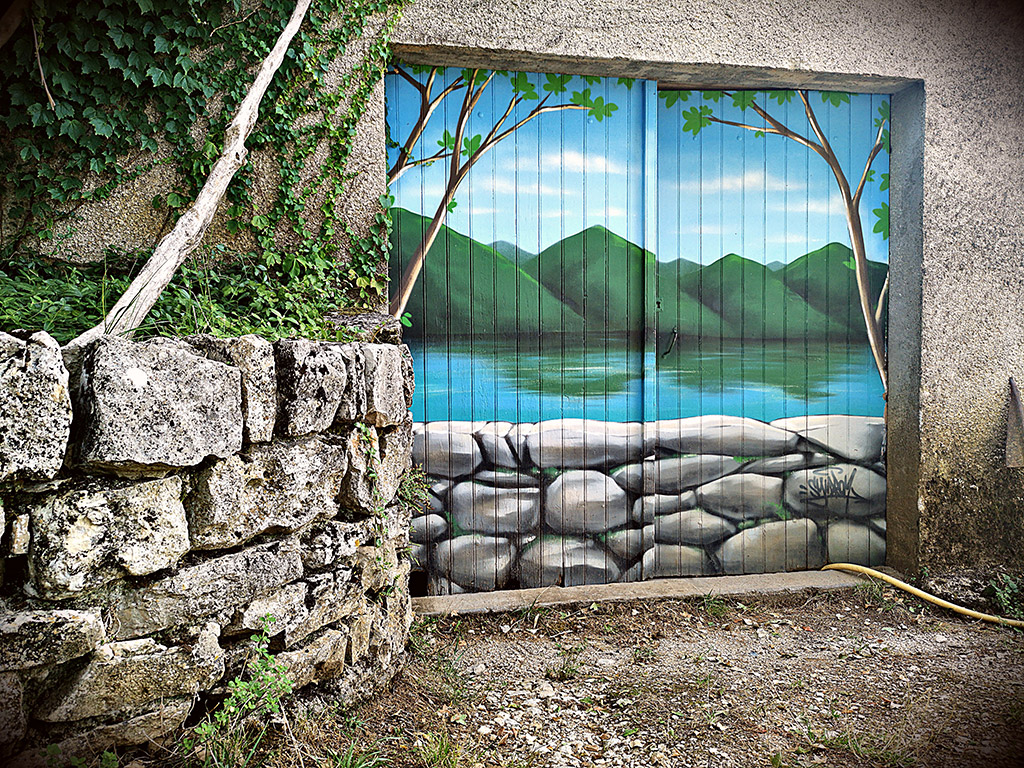 Fresque décorative, paysage de montagnes en trompe l'œil sur porte de garage.